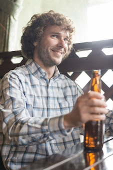 Smiling man with beer looking away