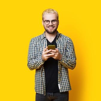 ブロンドの髪と眼鏡をかけているひげを持つ笑顔の男は、黄色のスタジオの壁でモバイルでチャットしています