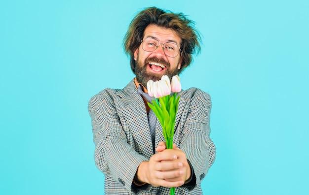 女性の日のためのチューリップの花束を持つ笑顔の男。