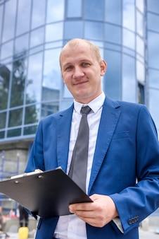 Улыбающийся человек с буфером обмена в костюме позирует перед бизнес-центром