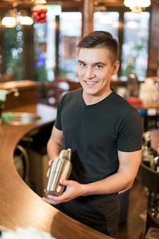 Smiling man with cocktail shaker