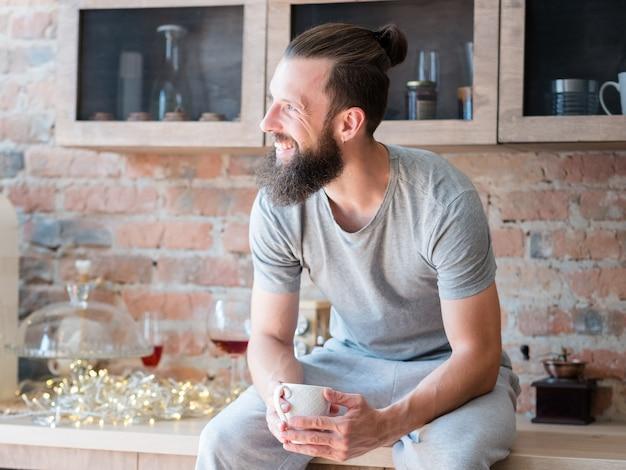Улыбающийся человек с чашкой сидит на кухонном столе и смотрит в сторону.