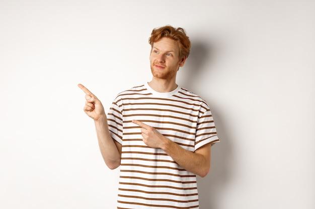 巻き毛の赤い髪の笑顔の男、縞模様のtシャツを着て、笑顔で指を左に向け、バナーを示し、白い背景の上に立っています。