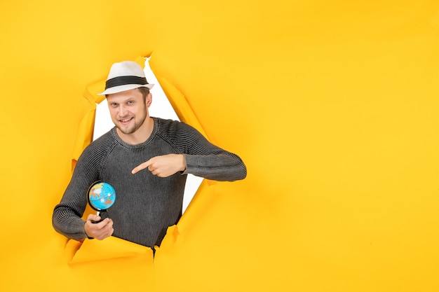 Uomo sorridente con un cappello che tiene un piccolo globo e che punta un piccolo globo in un muro strappato sul giallo