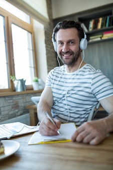 Smiling man with headphones writing in his diary at coffee shop
