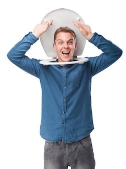 Uomo sorridente con la testa bloccato sulla cima di una toilette