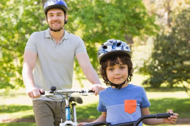 彼の息子が乗っている自転車で笑っている男