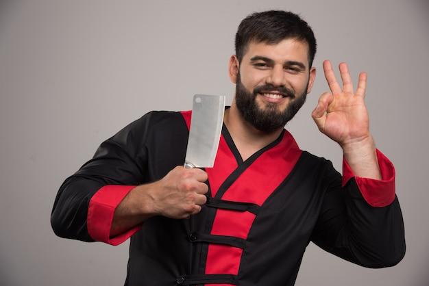 Улыбающийся человек с ножом, показывая хорошо жест.
