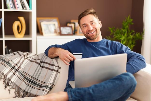 ノートパソコンとソファの上のクレジットカードで笑顔の男