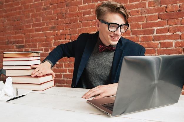 ノートパソコンで笑顔の男は本の山を移動します。