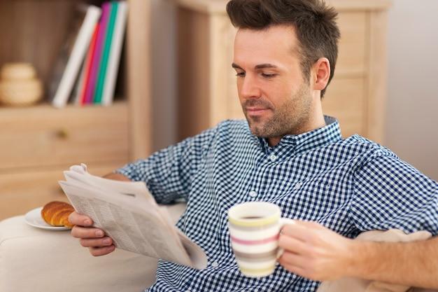 Uomo sorridente con giornale e tazza di caffè
