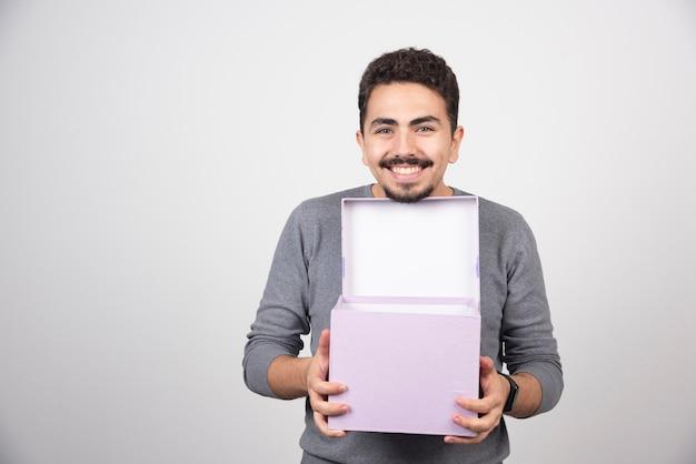 Uomo sorridente con una scatola viola aperta su un muro bianco.