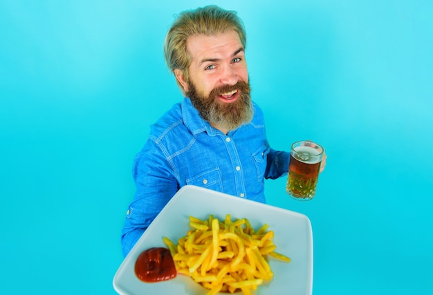감자 튀김과 맥주와 함께 웃는 남자. 감자튀김 감자. 감자 튀김과 케첩 접시에 수염된 남성.