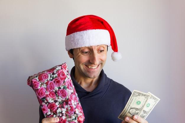Улыбающийся человек в красной шляпе санта-клауса держит завернутый подарок и долларовые купюры экономия денег на рождество gif