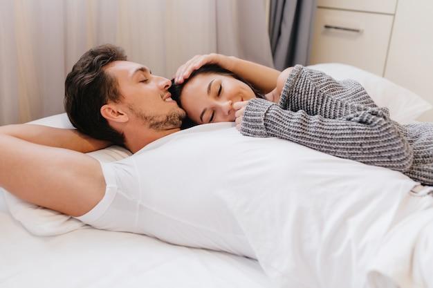 日曜日の朝、短い髪型の笑顔の男が女友達と目覚めた