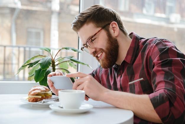 カフェで彼の昼食を撮影するスマートフォンで笑みを浮かべて男