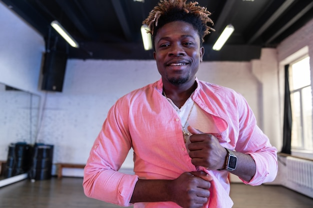 Smiling man with stubble and short dreadlocks scrunching his pink shirt
