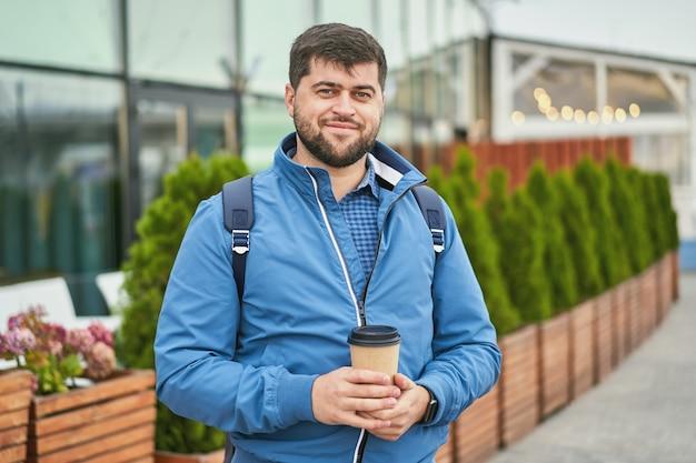 야외 손에 테이크 아웃 커피와 함께 웃는 남자.