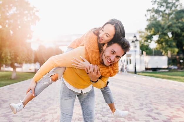 晴れた秋の日に友人のピギーバックを運ぶトレンディな髪型の笑顔の男