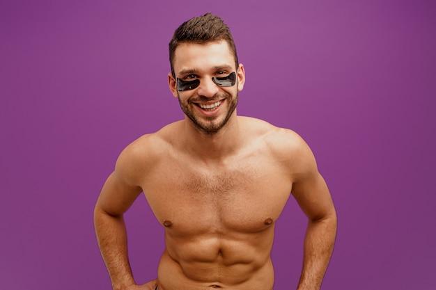 Улыбающийся человек с повязкой под глазом на лице. бородатый парень с идеальной кожей смотрит в камеру. концепция ухода за кожей лица. изолированные на фиолетовом фоне. студийная съемка. копировать пространство
