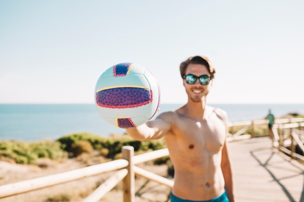 Smiling man with volleyball at the beach