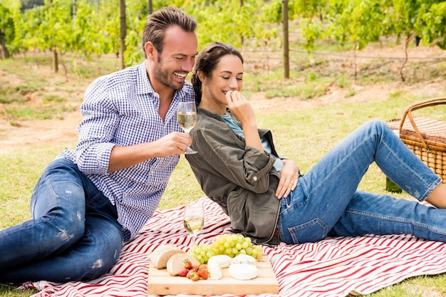 Smiling man with woman having wine at lawn