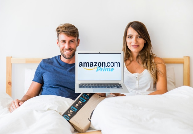 Smiling man and woman in bed with laptop