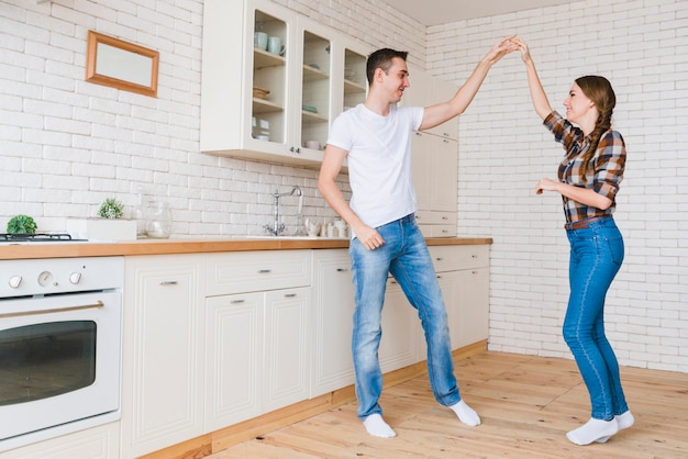 Smiling man and woman in love dancing in kitchen
