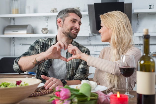 Smiling man and woman showing heart by hands and sitting at table in kitchen