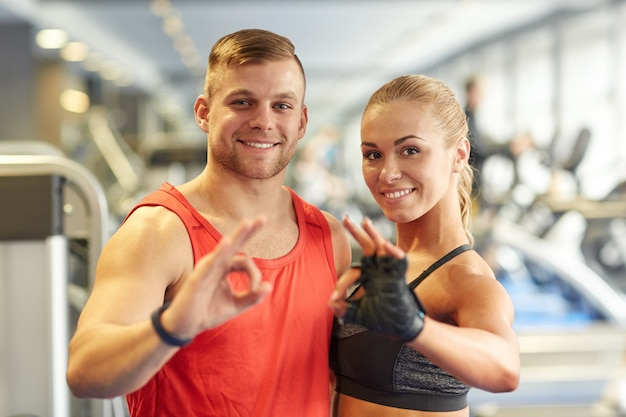 Smiling man and woman showing ok hand sign in gym