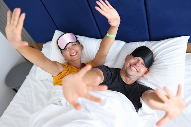 Smiling man and woman in sleep masks lie on bed comfortable sleep concept