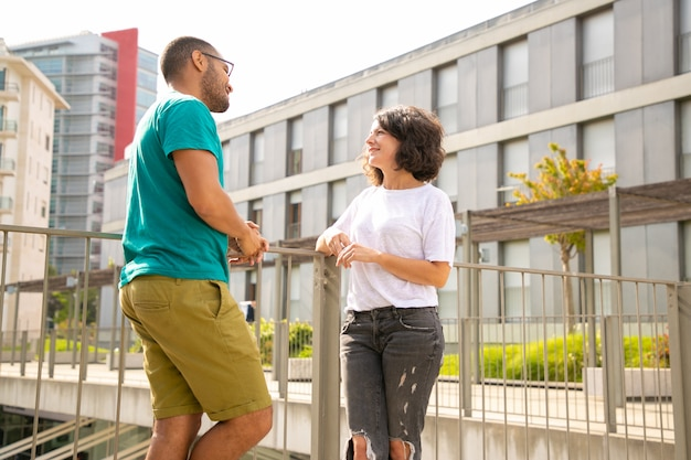Smiling man and woman talking on street
