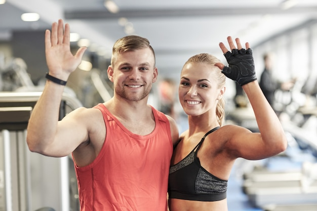 Smiling man and woman waving hands in gym