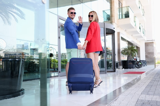 Smiling man and woman wearing sunglasses with suitcase near building