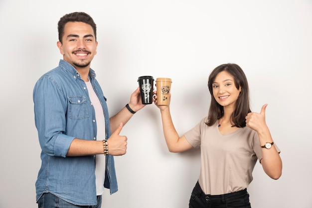 Smiling man and woman with cups of coffee and showing thumbs up.