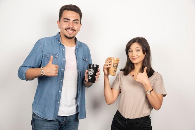 Uomo e donna sorridenti con tazze di caffè.