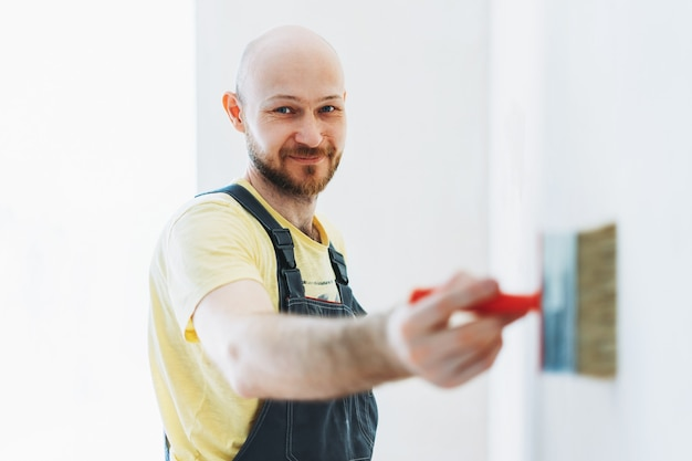 Smiling man worker in overalls do repair glue the walls under the wallpaper or primer on wall selective focus