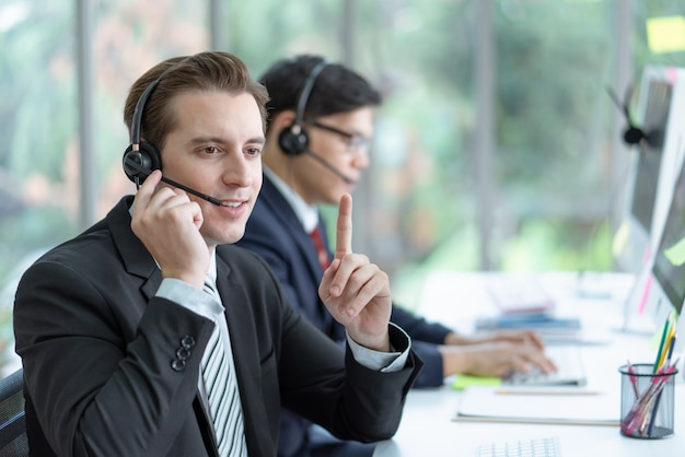 Smiling man working customer service wearing headphone talking with a customer at call center office.