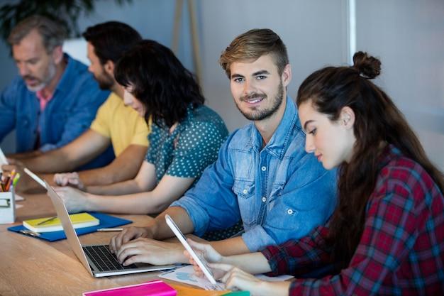 사무실에서 그의 창조적 인 비즈니스 팀과 함께 일하는 웃는 남자