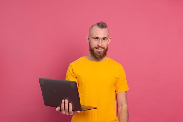 분홍색 배경에 고립 된 노트북으로 작업 웃는 남자