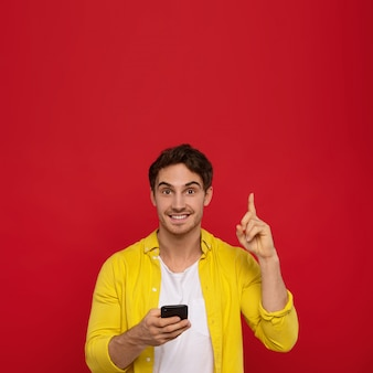 Smiling man in yellow shirt using smartphone and pointing with finger up, smiles positively,