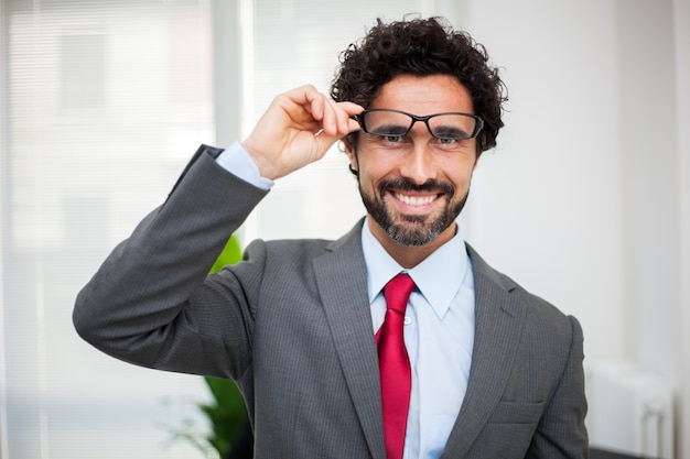 Smiling manager in his office holding his eyeglasses