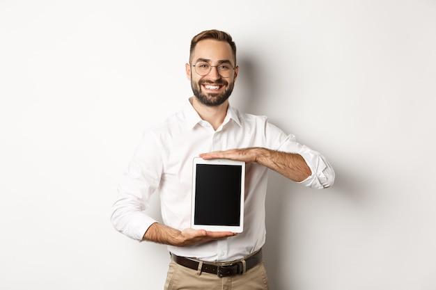 Улыбающийся менеджер показывает что-то на экране цифрового планшета, демонстрирует веб-сайт, стоя