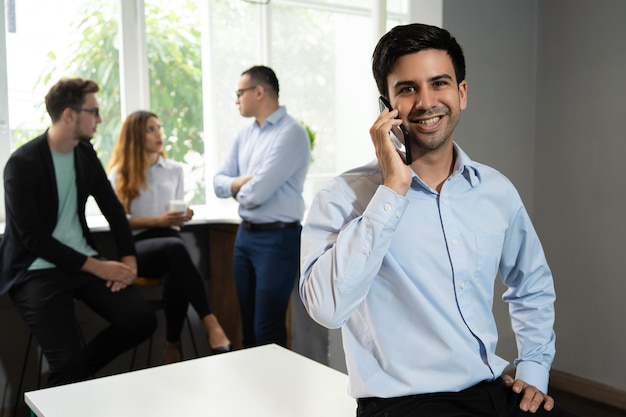Smiling manager talking on mobile phone