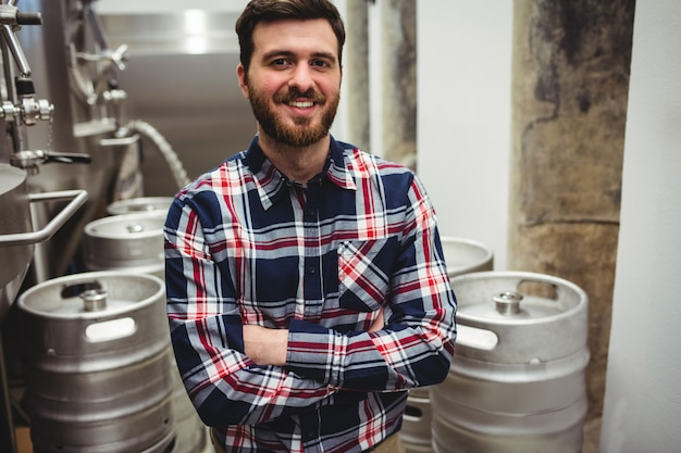 Smiling manufacturer standing in brewery
