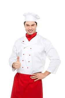 Улыбающийся шеф-повар показывает палец вверх стоя на белом.
