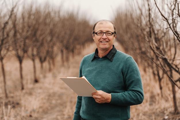 Усмехаясь зрелый взрослый кавказский лысеющий агроном стоя в саде, держа доску сзажимом для бумаги и смотря камеру.