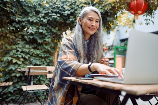 Smiling mature asian woman eats strawberry dessert working on laptop at table outdoors