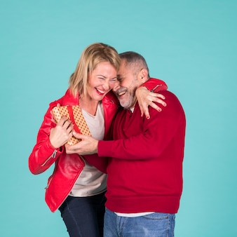 Smiling mature blonde woman embracing her husband holding wrapped present against colored backdrop