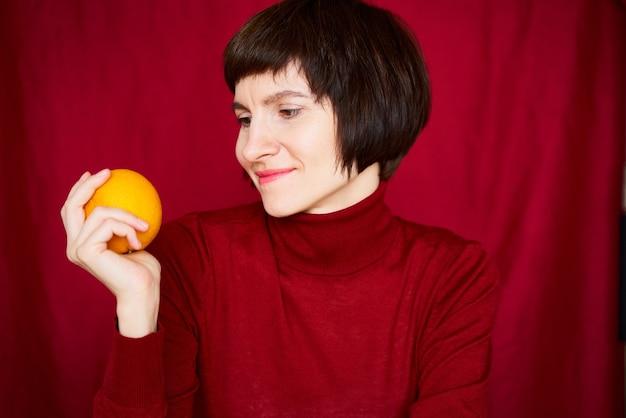 Улыбается зрелая брюнетка женщина, глядя на апельсиновый фрукт в руке крупным планом лицо портрет поколения x